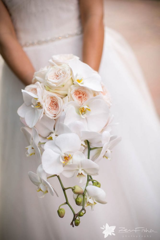 Bride holding bouquet featuring white orchids