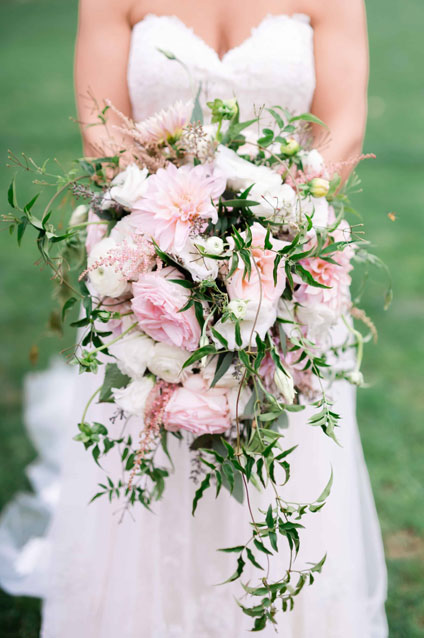 Bride holding a pink and white cascading bridal bouquet.